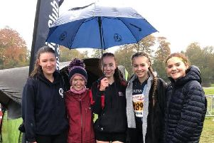 Sheltering under an umbrella are five of the Buxton juniors who took part in the National Cross-Country Relays.