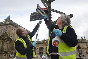 John and Tina Heathcote cleaning a signpost in The Crescent.