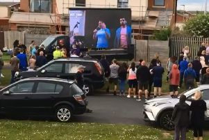 People watch a screen at the Tommy Robinson rally.