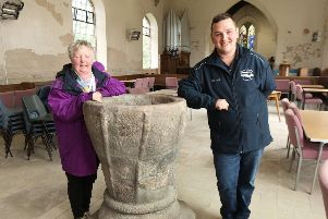 Angela Campeau and Jason Bentley with the ancient Saxon Font that survived the bombing and attracts interest from many visitors