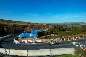 A cyclist climbs out of Swaledale  over the rebuilt bridge, which was washed away the the floods last month, across Grinton Moor on the Elite UCI World Championship Course