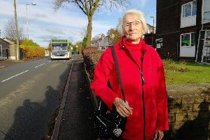 Joan Linden has trouble navigating the narrow path outside her home