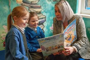 Head teacher Anne Ingle in one of the school's many reading areas with pupils Lilia Baker and Isla Tuck.