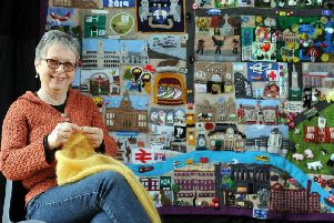 Sandra Dennis from the North Leeds Knit and Natter group with the Knitted Leeds hanging.