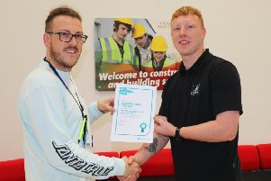 Will Holmes (right) is presented with his award by tutor Adam Thompson