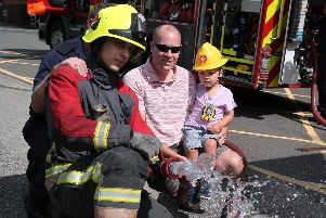 Simon Ormrod and his son Freddie watch as Fire fighter George Sargeant use the fire hose.