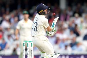 England's Jos Buttler is hit in the face by the ball.