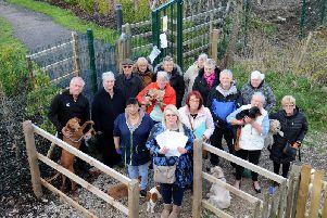 Residents gather to protest against the closure of the footpath