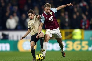 Burnley's Charlie Taylor forces his way past Daniel James in victory over Manchester United at Old Trafford