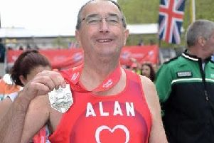 Alan proudly shows off his medal after completing the London Marathon