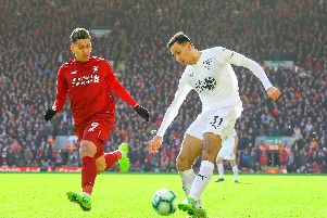 Burnley's Dwight McNeil takes on Liverpool's Roberto Firmino at Anfield