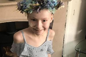 Brave Tia Taggart poses in a dress and garland of flowers sent to her by a well wisher for her 10th birthday.