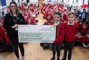 Imogen Osbaldeston with her brother Jude presents the cheque to Lily Preston, community fundraising officer from Royal Manchester Children's Hospital.