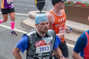 Adam on his way to completing the London Marathon wearing a lead vest weighing a stone.