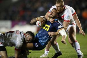 Luke Thompson gets to grips with the Wigan defence in the opening game of the season