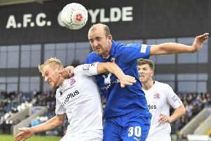 Chesterfield's Tom Denton wins a header against AFC Fylde