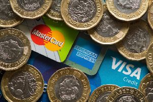 Mastercard, American Express and Visa credit cards with UK one pound coins.