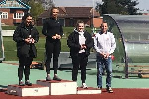 Charlotte Williams on top of the podium with coach Michael Hitchon, father of Olympic bronze medalist Sophie Hitchon