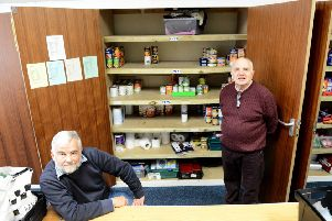 Granville Hawkins (right) with Elim Church Foodbank volunteer Dave Smith in front of a near empty food cupboard after this week's foodbank