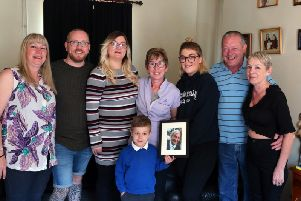 Oscar Hardwick holds a picture of his great-grandmother Maureen Yeomans surounded by family members, left to right, Sharon Stott, Craig Porter, Lian Hardwick, Sue Porter, Chloe Porter, Phil Bradbury and Jeanette Yeomans. Picture by Eric Gregory.