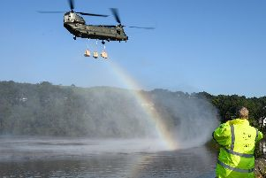 A Chinook helicopter creates a rainbow in the spray as it prepares to drop sandbags onto the dam wall at Toddbrook reservoir. Photo by Leon Neal/Getty Images