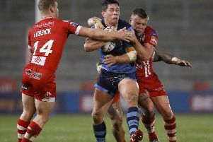 Saints' Louie McCarthy-Scarsbrook is tackled by Salford Red Devils' Joey Lussick (left), Junior Sa'u (centre) and Salford Red Devils' Josh Jones