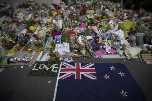 Mourners lay flowers on a wall outside the Al Noor mosque in Christchurch, New Zealand