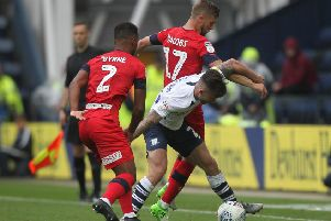 Sean Maguire takes the ball between Wigan's Nathan Byrne and Michael Jacobs at Deepdale