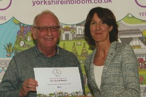 Council chairman, Coun Ian Lloyd, receives the In Bloom gold award for Harthill with Woodall.