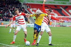 Paul Downing and Matty Blair tussle with Lyle Taylor.