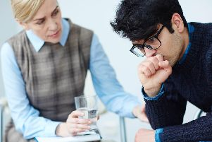 Young depressed man wearing sweater and glasses opening up to his psychologist about mental problems