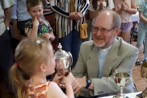 Isabella Ribbert receives the Breffit Trophy from Rev Tim Parker.