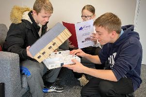 A scale model of the plans for a new Fleetwood youth centre are examined by young people from The Boathouse Youth project