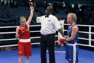 The referee holds aloft the arm of Gemma Richardson to signal her victory.