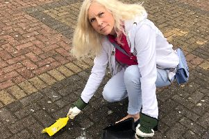 Councillor Melanie Darrington cleaning up broken glass in Skegby.