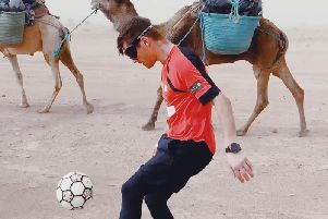 John juggles a football across the desert