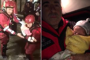 Firefighters rescue a one-year-old and seven-week-old twins from a flooded house in Elland (Picture West Yorkshire Fire and Rescue Service)