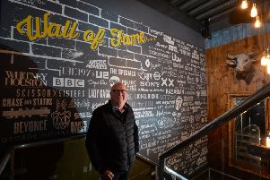 Producation Park founder Adrian Brooks, in front of a wall of fame listing acts and clients the park's companies have worked with.