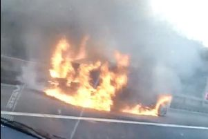 Cars speed past a burning car on the M62 this morning.
