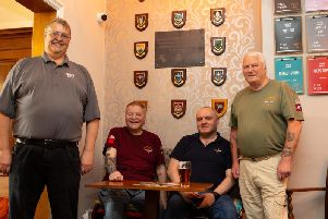 Steve Francis, Jay Jay Johnson, Phil Hull and Paul Boyd, with the wall of war veterans' plaques.