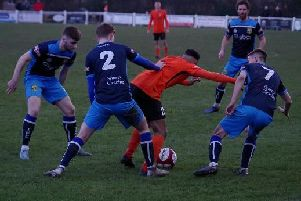 A trio of Tadcaster Albion players attempt to take the ball off a Brighouse attacker