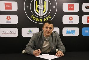Scott Brown puts pen to paper on his deal with Harrogate Town. Picture: Matt Kirkham
