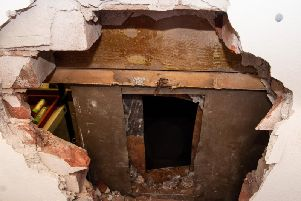 The  gaping hole in the wall and the safe with its back drilled off after the raid at Burnley Auctioneers