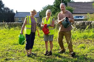 Sarah, Tracey and Tim from the Pateley Bridge in Bloom group water the wildflower meadow.