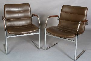 A pair of cantilevered tubular chrome and leather chairs.
