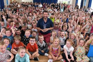 Dave McPartlin, surrounded by pupils at Flakefleet Primary School,  with his Community Excellence Award