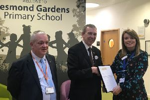 Mike Hill presents the award to Jesmond Gardens' parent support advisor Carly Lupton with chairman of governors Peter Ingham looking on.