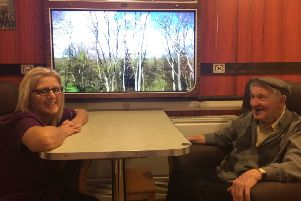 Wynards Woods care home resident Ron Murray (right) and care assistant Janet Robinson by the train carriage feature to help people with dementia.