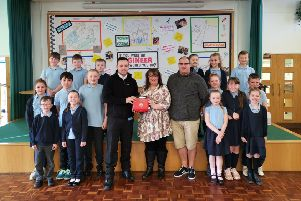 Adam Goodwin and Paul Foster of Defibs4Hartlepool with staff and pupils at Kingsley Primary School.