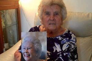 Minnie Nichol celebrating her 100th birthday with a card from Her Majesty the Queen.